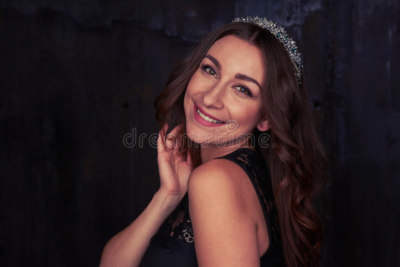 Elegant woman with curly hair and a diadem smiling over her shoulder at the camera stock image