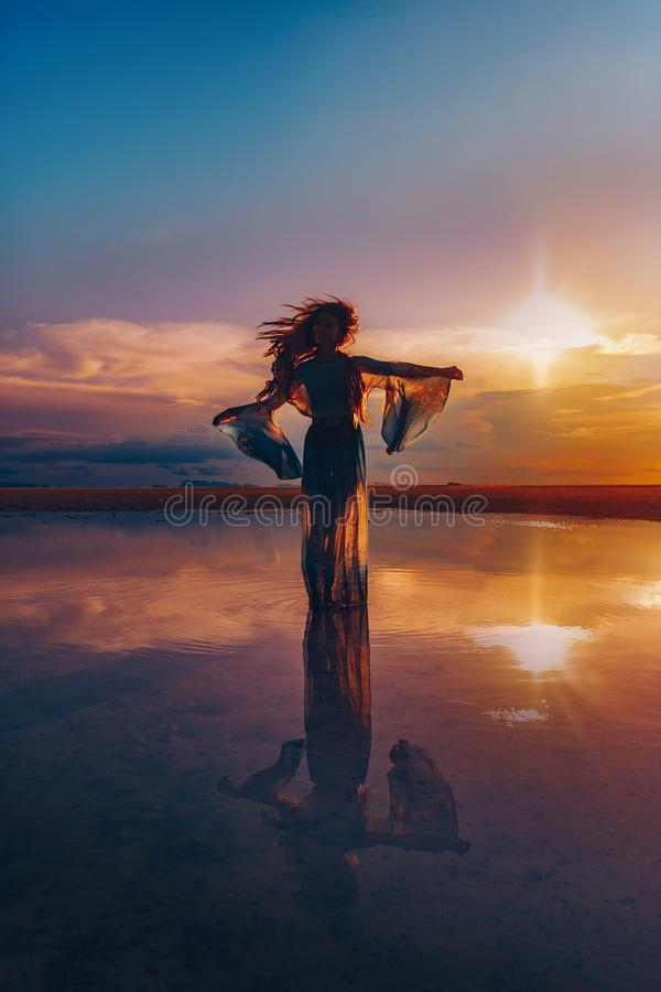 Elegant woman dancing on water. Sunset and silhouette royalty free stock image