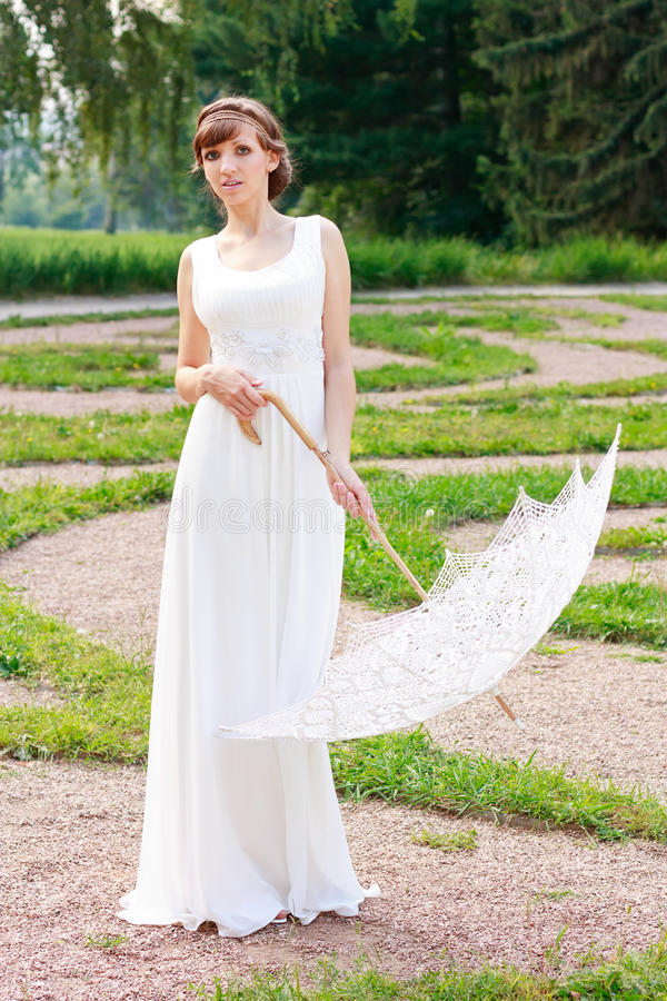 Elegant woman with decorative umbrella in vintage. White elegant woman in white dress with decorative umbrella in a vintage style against background green nature royalty free stock photos