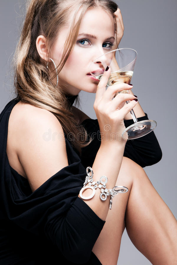 Elegant woman drink martini coctail. Blond elegant woman drinking martini, studio shot royalty free stock photography
