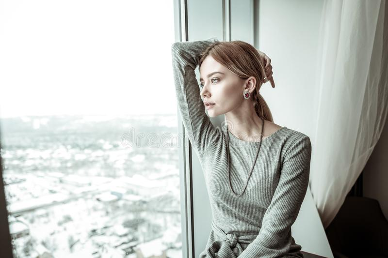 Elegant fashionable blonde-haired woman looking into window stock images