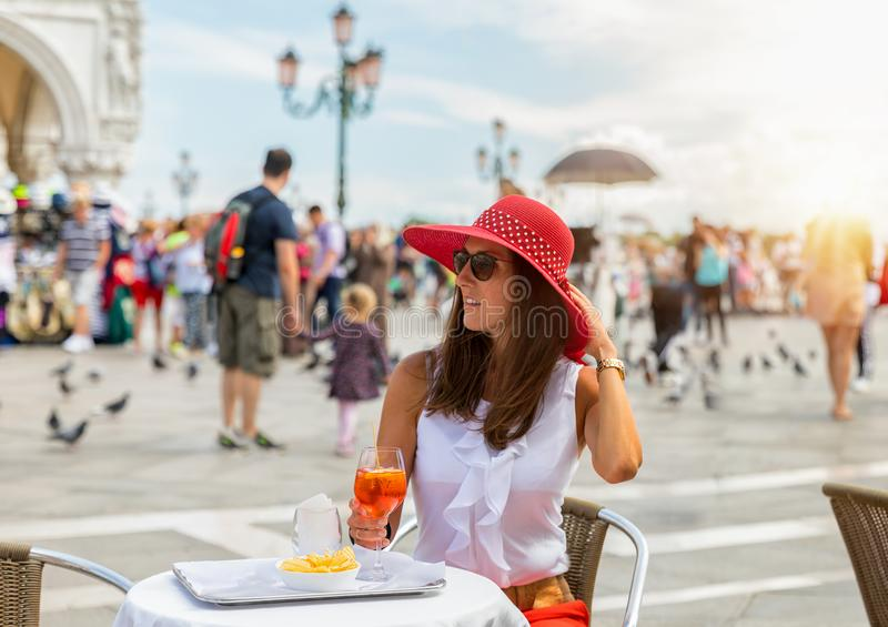 Elegant woman enjoys an Aperitif on the St. Mark`s Square in Venice. Elegant woman with a red hat enjoys an Aperitif on the famous St. Mark`s Square in Venice royalty free stock photos