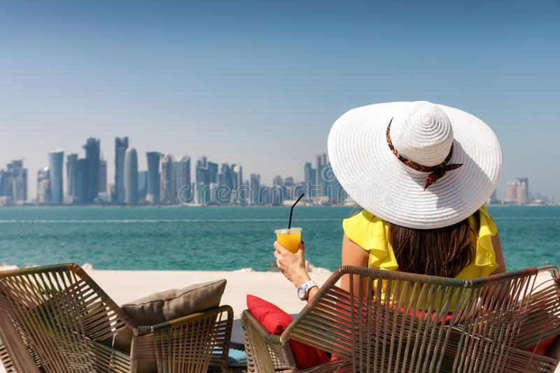 Elegant woman enjoys the view to the skyline of Doha, Qatar royalty free stock photos
