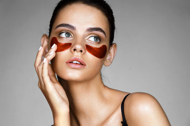 Elegant woman with eye patches showing an effect of perfect skin. royalty free stock photos
