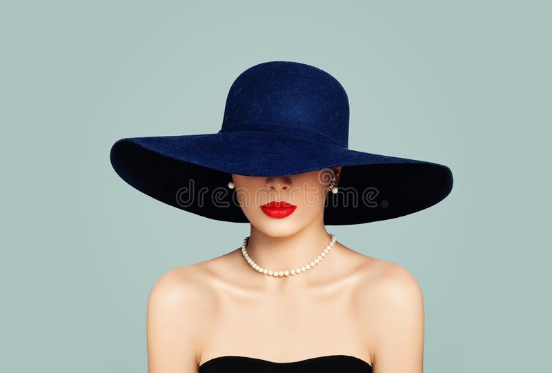 Elegant woman fashion model with red lips makeup wearing classic hat and white pearls, portrait stock image