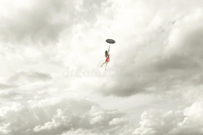 elegant woman flying in the middle of the clouds hanging on her umbrella stock photography