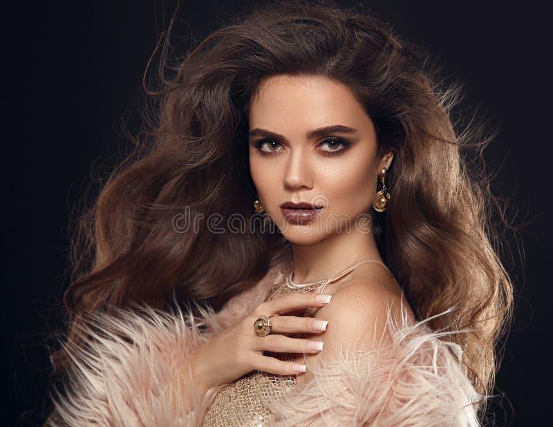 Elegant woman in fur coat. Beautiful girl with long wavy hair st stock photos