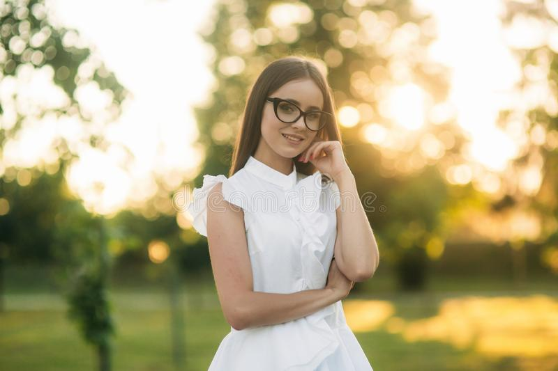 Elegant woman in glasses standing in the park and looking through glasses. Female model stock images