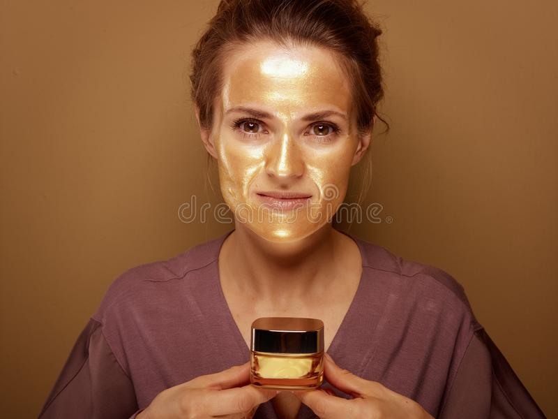 Elegant woman with golden mask holding bottle of facial creme royalty free stock image