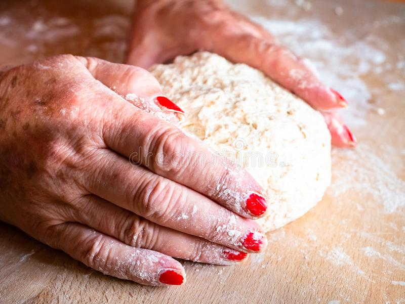 Elegant woman hands kneading and massaging homemade bread dough. Italian tradition, made of whole wheat flour, on wooden board stock photography
