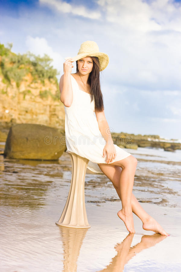 Download Elegant Woman With Hat Sitting At The Beach Stock Photo - Image: 19891388