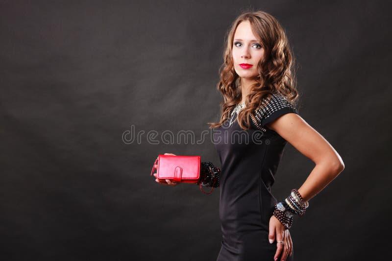 Elegant woman holding red handbag clutch bag. Fashion elegant evening outfit. Close up elegant woman holding red leather handbag clutch bag on dark background royalty free stock photos