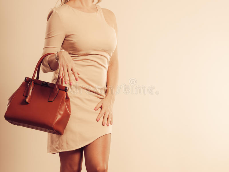 Elegant woman holds brown handbag royalty free stock photos