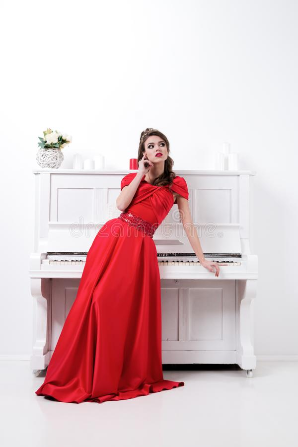 Elegant woman in long red dress standing in white room near piano. Copy space. European tall girl with makeup. Beauty lifestyle c stock photo