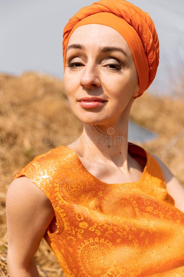 Elegant Woman in Oriental Dress and Turban in Dry Grass royalty free stock photo