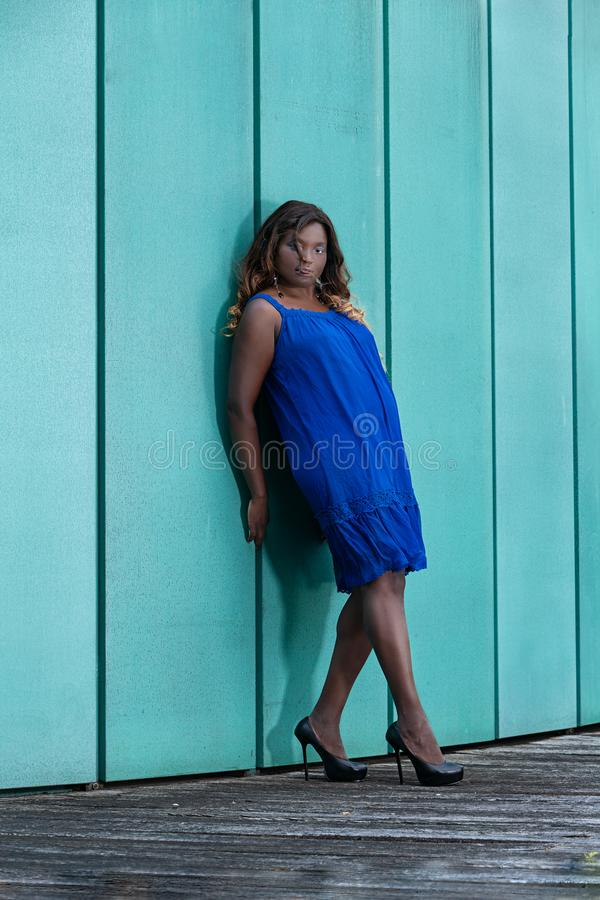 Elegant woman with oversize. Woman with oversize is leaning against a wall in a summer dress stock photos