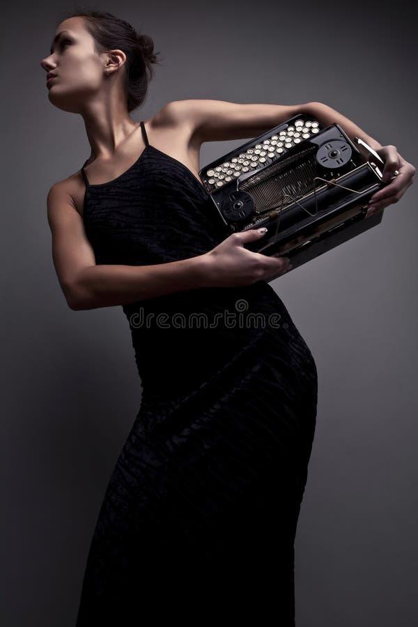 Elegant woman pose with ancient typewriter. Conceptual fashion photo. Elegant woman pose with ancient typewriter royalty free stock photo