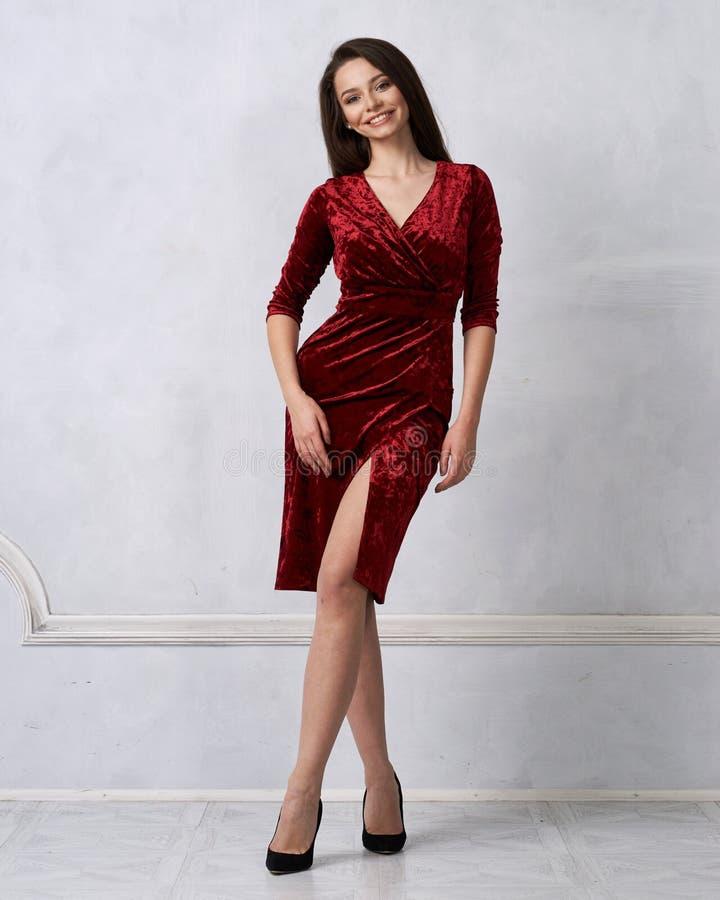 Elegant woman in red velvet midi dress royalty free stock image