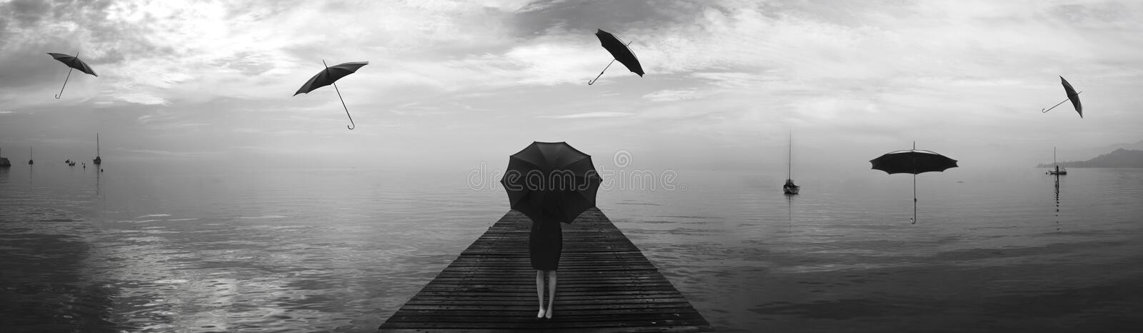 Elegant woman repairing from the rain of blacks umbrellas royalty free stock photo