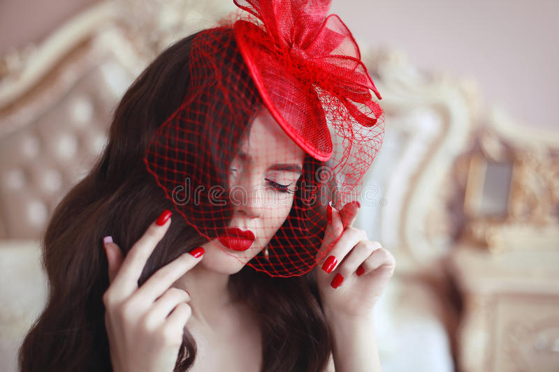 Elegant woman in retro hat with red lips and manicured nails. Br. Unette closeup portrait. Sensual female posing in luxury modern interior stock photos