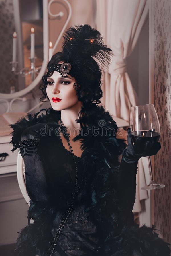 Elegant woman in retro style of the 20s, lady flapper in a black dress, dark hair and a bandage, feather boa, long stock images