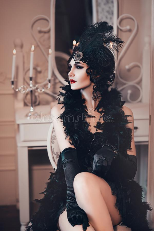 Elegant woman in retro style of the 20s, lady flapper in a black dress, dark hair and a bandage, feather boa, long. Gloves. image of a gangster girl on a party stock photos