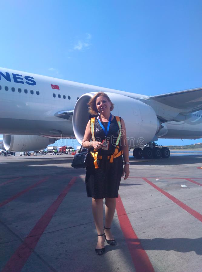 Elegant woman with safety vest on airport runway next to plane for passenger transfer. airport activity. stock photo