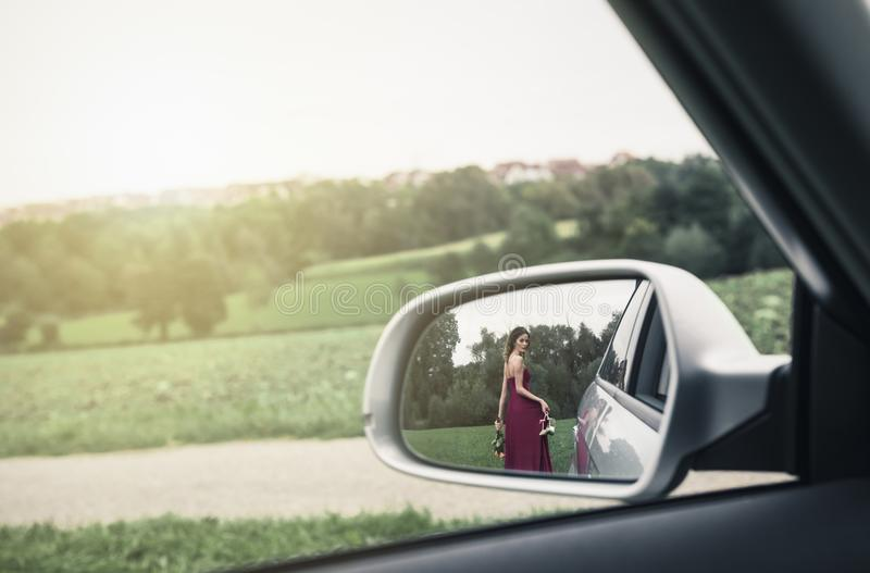 Elegant woman seen in the rearview mirror of car stock image