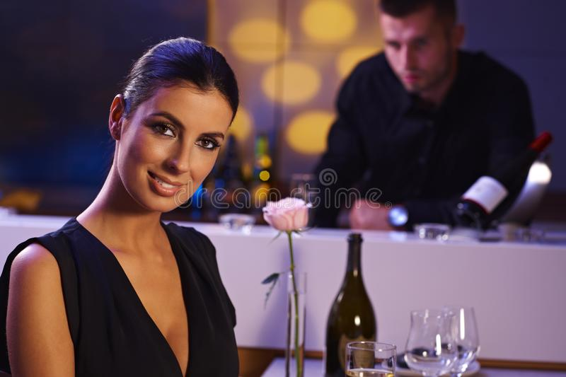 Elegant woman sitting in restaurant smiling royalty free stock photography