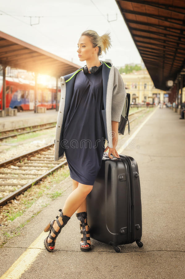 Elegant woman with suitcase posing on the railway station stock photo
