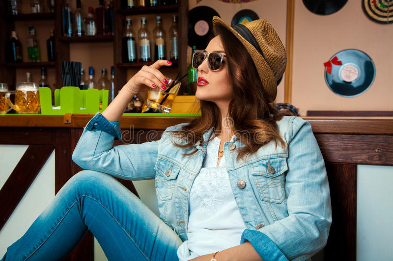 Elegant woman in sunglasses and hat drinking cold alcohol cocktail in bar stock image