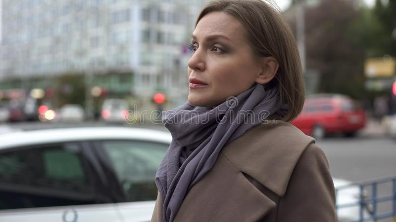 Elegant woman waiting long time for public transport on stop, autumn in big city stock photography