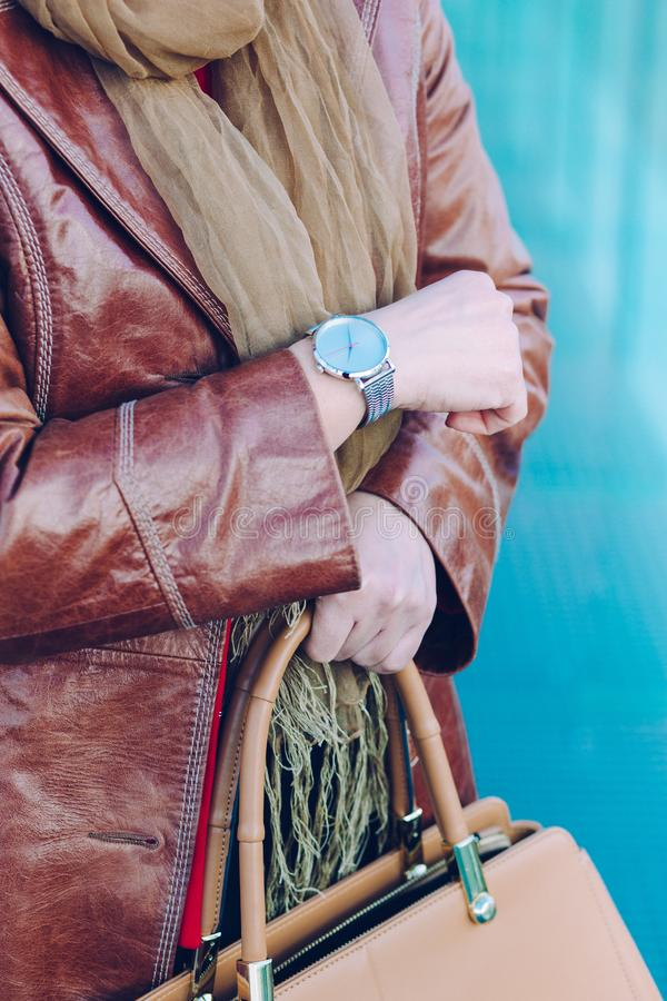 Woman wearing silver wristwatch and brown leather coat holding l stock image