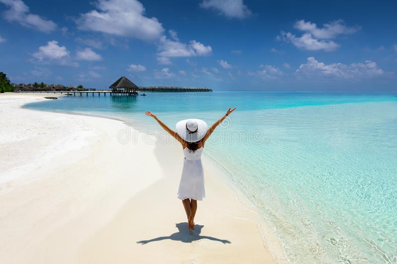 Elegant woman in white walks on a tropical beach in the Maldives royalty free stock image