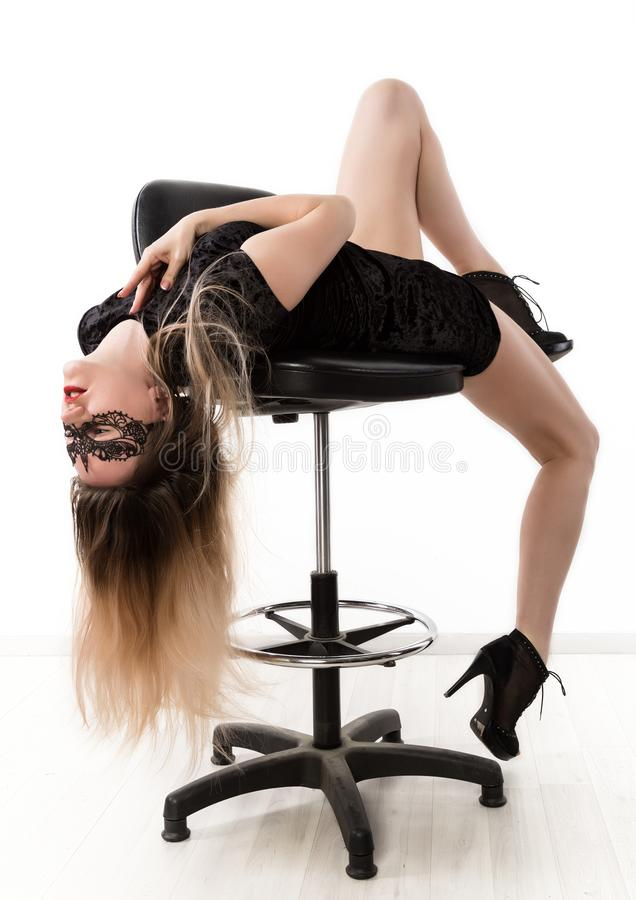 Free Elegant Womanin A Little Black Dress Is Posing While Sitting On A High Chair And Spreading Her Legs. Girl On A Stock Photo - 139973140
