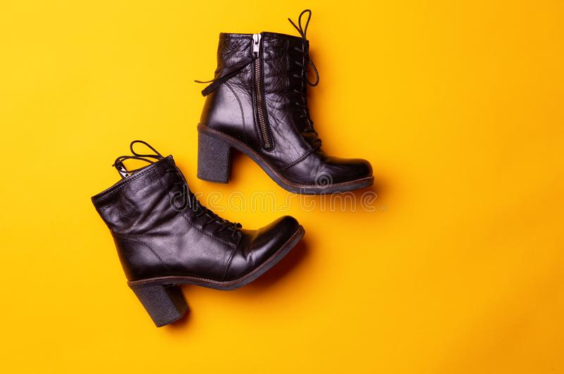 Elegant women black heeled boots. Top view of black boots on a yellow background. stock photos