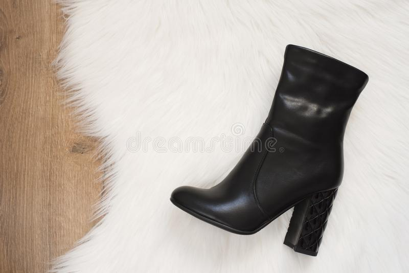 Elegant women black high heeled boots. Top view of black boots on a white fur carpet, wooden background. Concept of fashion and de royalty free stock photos