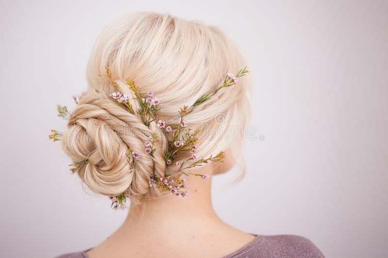 Elegant women`s hair styles for blonde hair. Beautiful young woman stock photography
