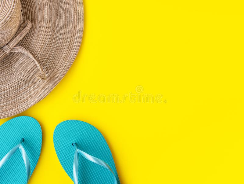 Elegant women`s straw hat with bow blue slippers on bright sunny yellow background. Beach vacation fashion travel relaxation fun royalty free stock image