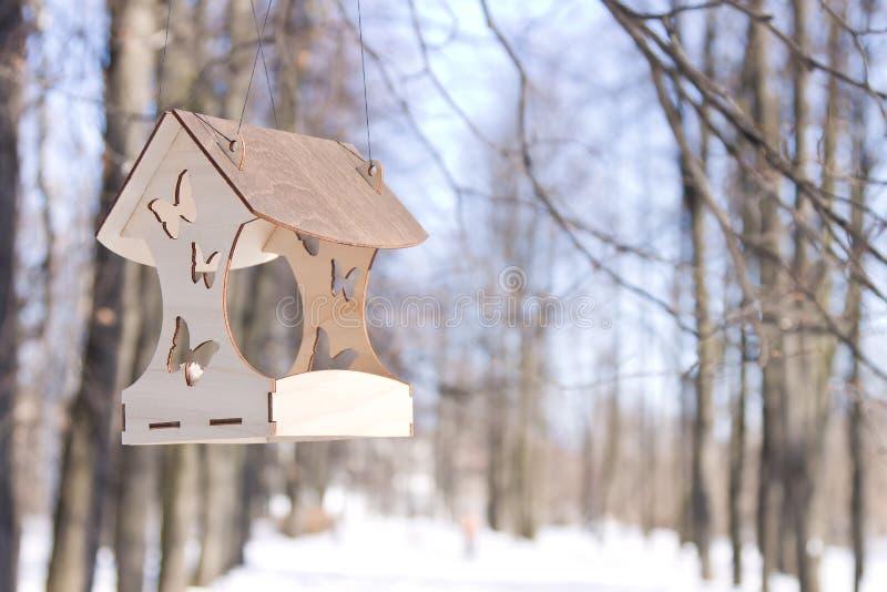 Elegant wooden bird feeder hanging on tree branches in winter park. Elegant carved wooden bird feeder hanging on tree branches in winter park royalty free stock image