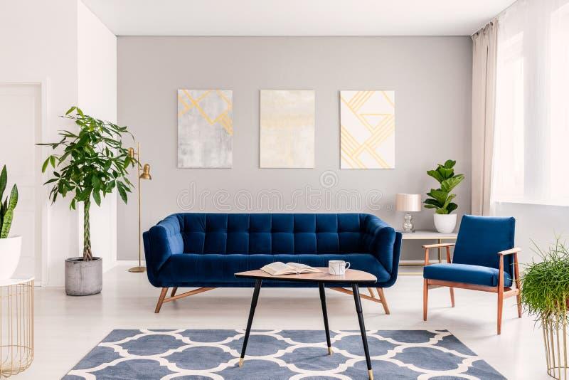 Elegant woonkamerbinnenland met een reeks van donkerblauwe bank en leunstoel Gouden en zilveren eigentijdse schilderijen op de ac royalty-vrije stock foto
