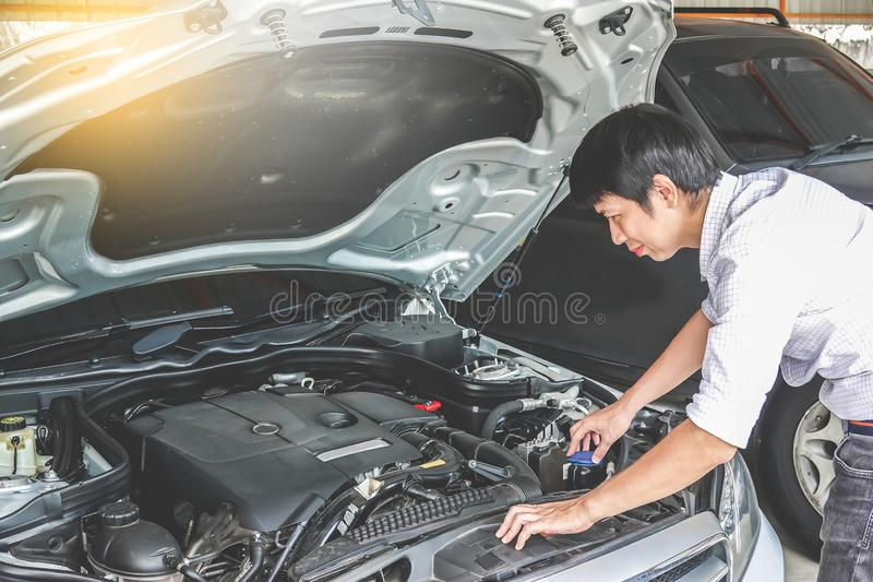 Elegant worried businessman is looking under the car hood trying to figure out the problem while leaning against the car royalty free stock photography