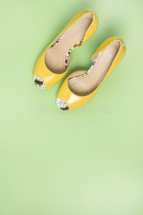 Elegant Yellow Female Leather Shoes on Summer Green Background Flat Lay Top Vew Copy Spac Sales Fashion Concept Vertical.  royalty free stock image