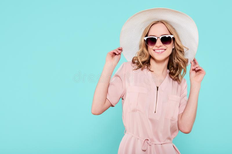 Elegant young attractive woman wearing pale pink summer dress, straw hat and sunglasses, thinking about her summer vacation. royalty free stock photo