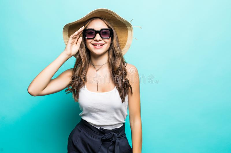 Elegant young attractive woman wearing summer clothes, straw hat and sunglasses, thinking about her summer vacation. Side view of stock photography