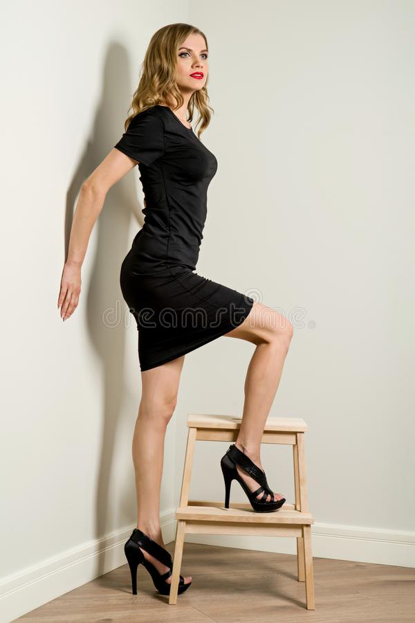 Elegant young business woman blond in black dress, Poses beside a stool stairs royalty free stock image