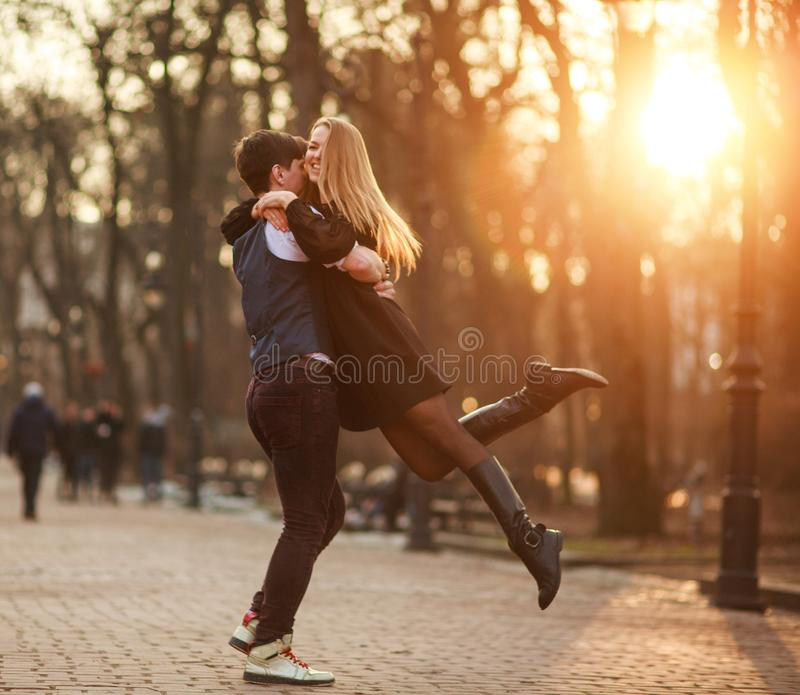 Elegant young couple in love in classic style passionately dancing in city park stock images
