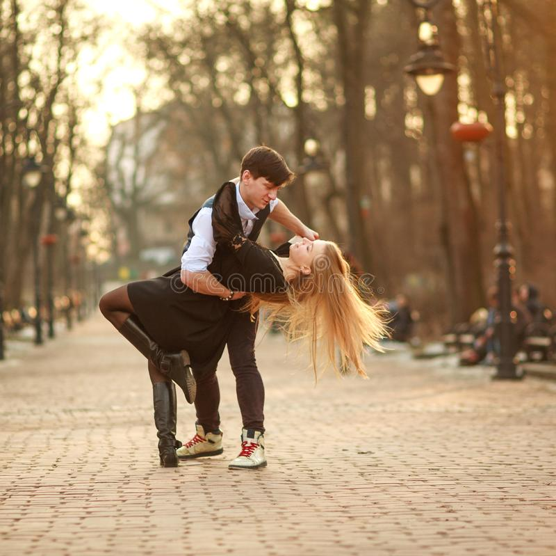 Elegant young couple in love in classic style passionately dancing in city park royalty free stock images