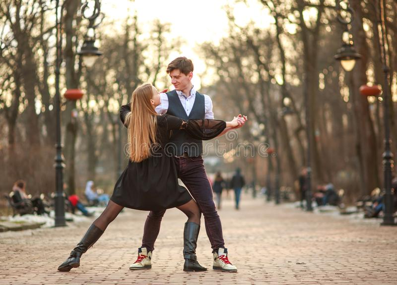 Elegant young couple in love in classic style passionately dancing in city park stock photo