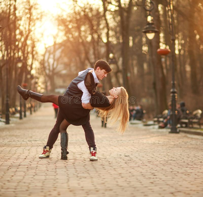 Elegant young couple in love in classic style passionately dancing in city park royalty free stock photography